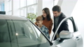 Young family with child buying car in dealership, man and woman doing high-five 62973614