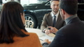 Happy couple purchasing car signing contract doing high-five talking to sales manager 62974654