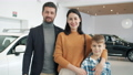 Slow motion of happy family with son smiling in car dealership standing together 62981586
