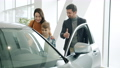 Cheerful couple and child purchasing car in showroom doing high-five opening auto door 63001127