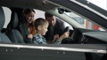 Slow motion of cheerful people mom, dad and kid choosing car, boy playing with steering wheel 63011433