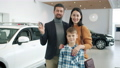 Slow motion portrait of mother, father and son smiling in car dealership holding key fob 63012440