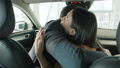 Slow motion of man and woman hugging inside beautiful new car in dealership 63013768