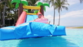 slow motion of asian girl playing on an inflatable slide in aquapark 63015858