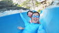 slow motion of asian girl with her dad enjoys water slide ride and take selfie in aquapark 63015860