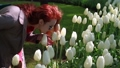 beautiful red-haired girl with glasses sniffs white tulips 63509147