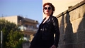 A beautiful red-haired woman in a black leather jacket and glasses 63566142