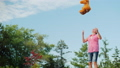 A young woman jumps on a trampoline and throws up a teddy bear. Active and healthy lifestyle 63585212