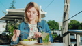 A young woman is eating a salad on the summer terrace in a restaurant. Eat Outdoors 63585215