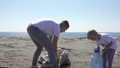 family picks up trash from the beach in trash bags 63593463