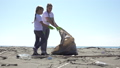 family picks up trash from the beach in trash bags 63593464