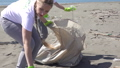 family picks up trash from the beach in trash bags 63593465