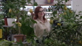 growing flowers, female farmer in glasses for vision examines state of decorative plant with fruits while working in greenhouse 63616088