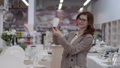 beautiful shopper with glasses for female vision chooses crockery for set of dishes in department store with household goods, design concept 63616270