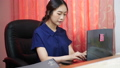 Woman working at home while typing on computer	 63659278