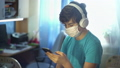 A teenager in the room with headphones listening to music and looking at the phone under quarantine for self-isolation. China coronovirus Covid 19. Portrait of a boy with a disposable medical mask. 63802315