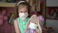 Portrait little girl with a rabbit toy in disposable face masks under quarantine for self-isolation. Pandemic epidemic infection with china coronovirus Covid 19, ncov 2019. 63802316
