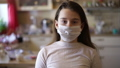 Epidemic, pandemic young girl stay at home under quarantine for self-isolation due to an infection with the china coronovirus Covid 19. Portrait of a girl with a disposable medical mask on her face. 63802317