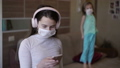 Epidemic young girl with sister looking at the phone and jump under quarantine for self-isolation, infection with china coronovirus Covid 19. Two girls with a disposable medical mask on their faces. 63802319