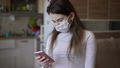 Epidemic young girl looking at the phone under quarantine for self-isolation due to an infection with the china coronovirus Covid 19. Portrait of a girl with a disposable medical mask on her face. 63802320