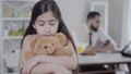 Portrait of upset Middle Eastern girl hugging teddy bear and looking at camera with blurred father at the background. Businessman ignoring sad daughter. Childhood, parenthood, family and business. 63824976