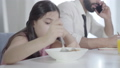 Close-up of cute Middle Eastern little girl mixing cereals with spoon as unrecognizable busy man talking on the phone at the background. Unhappy childhood, ignoring, lifestyle. 63824979