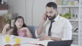 Portrait of busy Middle Eastern father ignoring little daughter eating breakfast. Young businessman talking on the phone while cute girl touching his hand. Lifestyle, multitasking, parenthood. 63824981