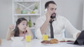 Middle Eastern little girl looking at father talking on the phone in the morning. Breakfast of busy man and bored daughter at home. Lifestyle, business and family, abandonment. 63824982