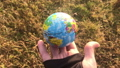 Female holding global earth in her hand, against yellow grass, ecology concept, human impact, save 64714139