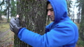 Young man in boxing gloves is hugging tree in forest and loving nature. man trying to treat his 64714161