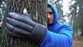 Young man in boxing gloves is hugging tree in forest and loving nature. Hands of adult caucasian 64714162