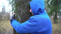 Young man in boxing gloves is hugging tree in forest and loving nature. Hands of adult caucasian 64714164