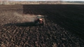 Aerial view of tractor plows the field in sunset, sunrise, raising dust, and behind it fly birds. Agriculture industry, cultivation of land. Food industry concept. 64847470