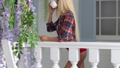 attractive blonde girl stands at the entrance to the house with a cup in her hands. beautiful white house with white railing and beautiful flowers. the girl drinks from a white cup 64870100