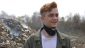 Portrait of young guy looks at camera on huge plastic landfill background. Ecological catastrophy 64873808