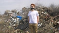 Portrait of young guy in a medical mask looks at camera on huge plastic landfill background. Ecological catastrophy 64873811