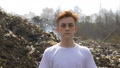 Portrait of young guy in a medical mask looks at camera on huge plastic landfill background. Ecological catastrophy 64874206