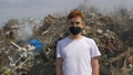 Portrait of young guy in a medical mask looks at camera on huge plastic landfill background. Ecological catastrophy 64874214