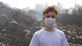 Portrait of young guy in a medical mask looks at camera on huge plastic landfill background. Ecological catastrophy 64874725