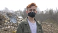 Portrait of young guy in a medical mask looks at camera on huge plastic landfill background. Ecological catastrophy 64875774