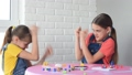 Two girls play board games and fight arcs with a friend 64925594