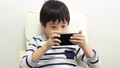A boy using a smartphone 64937278