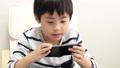 A boy using a smartphone 64937279