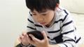 A boy using a smartphone 64937280