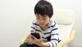 A boy using a smartphone 64937281
