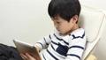 A boy using a tablet 64937284