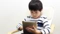 A boy using a tablet 64937285