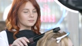 Beautiful red-haired master working with the hair of a client doing a curly hairstyle using a curling iron. The artist creates a curl hairstyle for long blonde hair in a beauty studio. 65016622