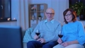 happy senior couple drink red wine and watch tv 65108627
