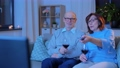 happy senior couple drink red wine and watch tv 65108628